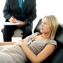 Young Woman with Her Hand on Her Belly and Man Beside Her Writing --- Image by © Royalty-Free/Corbis