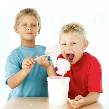 Two Young Boys (7-9) Eating Ice Cream Out of a Tub