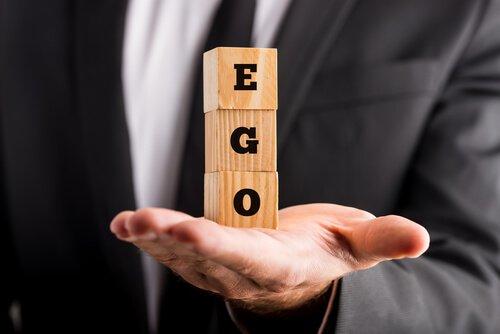 Hombre-sosteniendo-la-palabra-ego-en-unos-cubos-de-madera