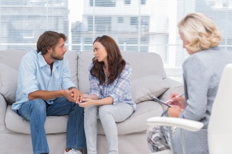 Therapist taking note while couple is speaking